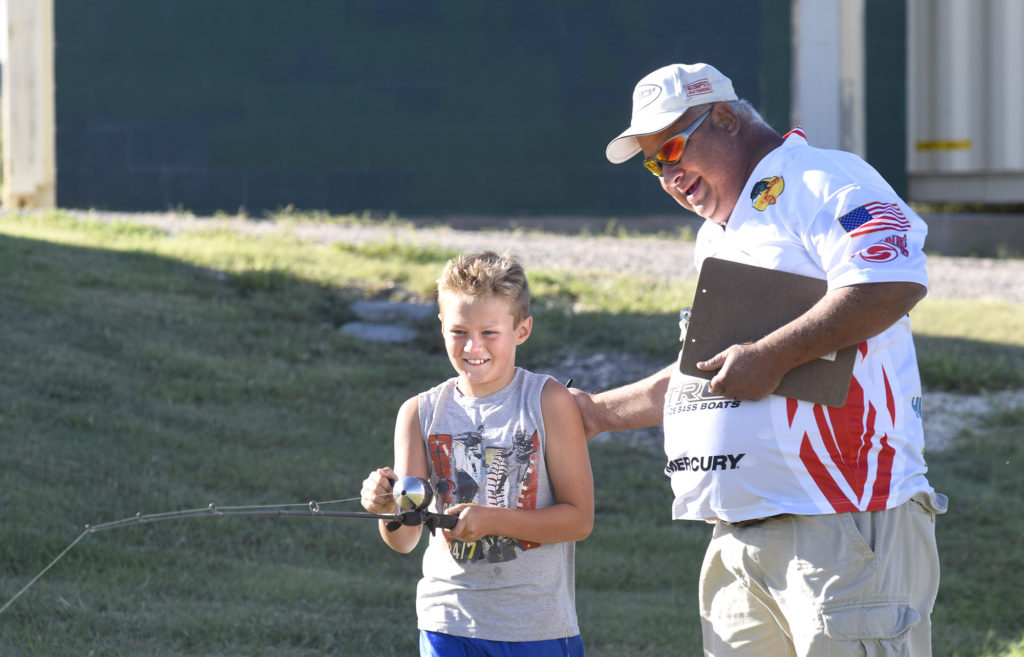 Mark Hladek of the Hays Bass Anglers Association, right, helps Alex Loving during the Kids Bass Casting competition on Aug. 20, 2016, at the Youth Outdoor Festival in Hays.